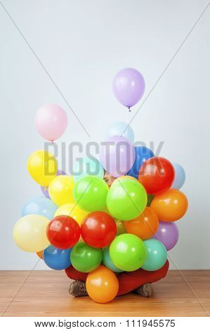 Woman hiding behind a huge bunch of balloons