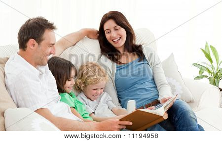 Happy Parents Looking At A Photo Album With Their Children