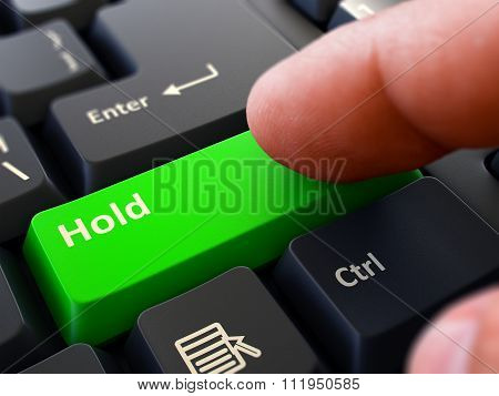 Pressing Green Button Hold on Black Keyboard.