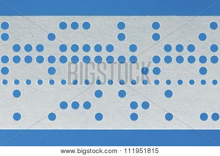 Closeup Of Perforated Punched Tape On Blue Background