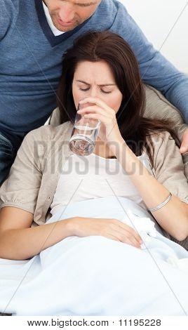 Sick Woman Drinking Water Lying On The Sofa