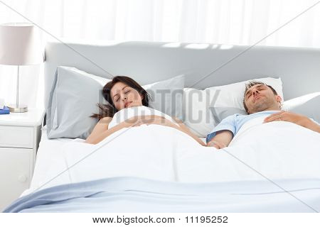 Lovely Couple Holding Their Hands While Sleeping On Their Bed