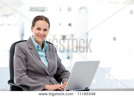 Young Manager Working On The Laptop Sitting At Her Desk