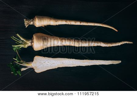 Fresh parsley roots on wooden cutting board