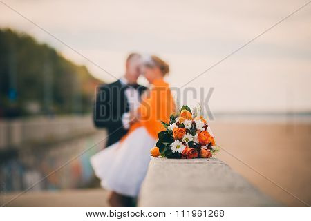 ginger wedding bouquet couple in background