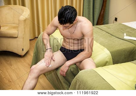 Young man applying body lotion to legs