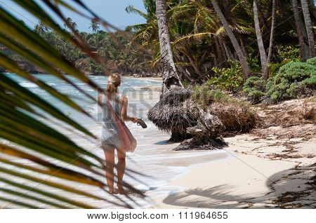Beautiful Blond Woman with pink bag walking barefoot along the lonely caribbean white sand beach and