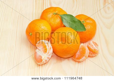 Several Mandarin Oranges On A Light Wooden Surface