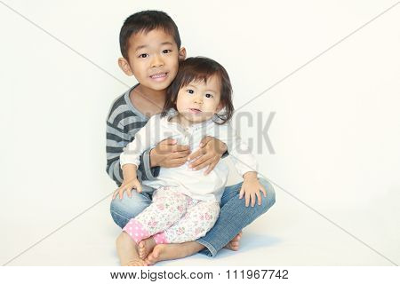 Japanese brother and sister sitting on his knee (6 years old boy and 1 year old girl)