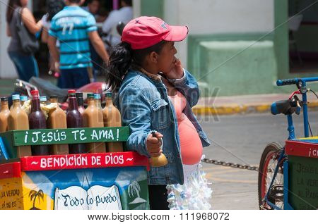 Woman with belly and pink baseball cap Vendor Selling Drinks on the streets