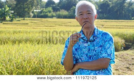 Asian Guy In Bright Shirt At His Sme Farmland. Abstract Own Agricultural Business.