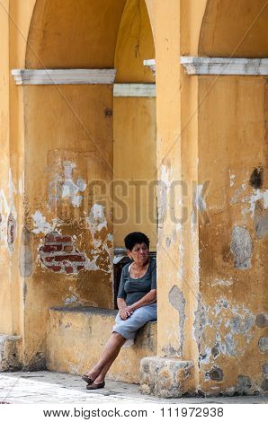 Woman Sitting on the Ledge of a yellow Hall