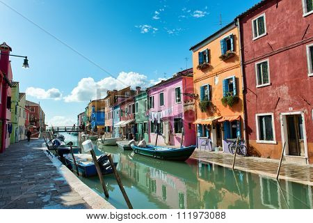 VENICE, ITALY - 17 OCTOBER 2015: Colorful houses with drying laundry hanging on the facades, Burano, Venice, Italy, painted in bright colors to guide the fishermen home in mist. 17 October 2015.
