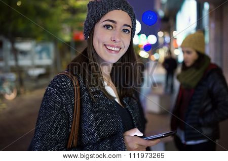 Portrait Of Beautiful Young Woman Using Her Mobile Phone At Night.