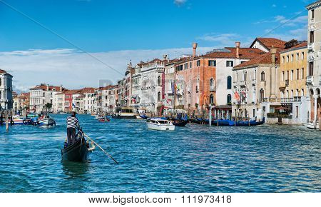 VENICE, ITALY - 17 OCTOBER 2015: Gondola taking tourists on a romantic tour of the city and boat traffic in the Grand Canal. Venice, Italy on 17 October 2015.