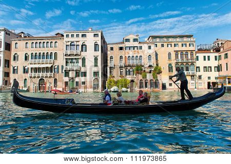 VENICE, ITALY - 17 OCTOBER 2015: Gondola with tourists being rowed by the gondolier on a romantic sightseeing tour of the Grand Canal. Venice, Italy on 17 October 2015.