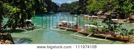 Traditional wooden filipino boats in a blue lagoon at tropical island