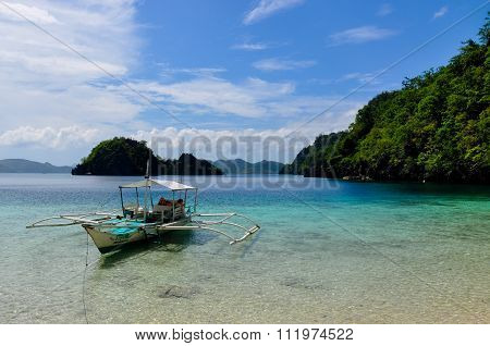 Traditional wooden filipino boat in a blue lagoon with crystal clear water at tropical island