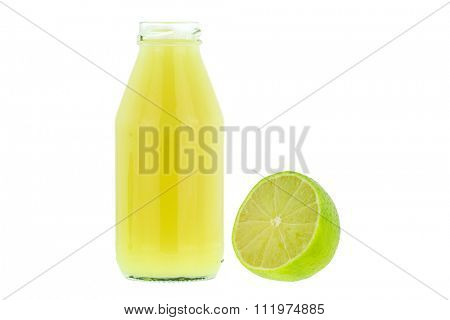 A bottle of lemon juice next to a huge seedless Tahiti hybrid lemons isolated on white background