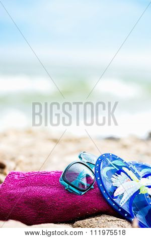 Summer Beach Holiday. Fuschia Towel, Sunglasses, Jelly Sandals Laying On The Sand