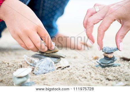 Hands Placing Stones On The Stone Pyramids On Sand