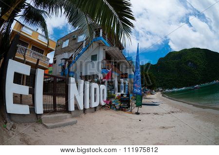 El Nido sign at the beach in front of houses