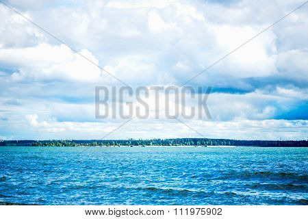 Blue Sea Front, Cloudy Sky, Sandy Beach And City On The Background