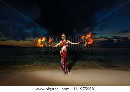 Tribal style girl on a tropical beach dancing with fire at sunset.