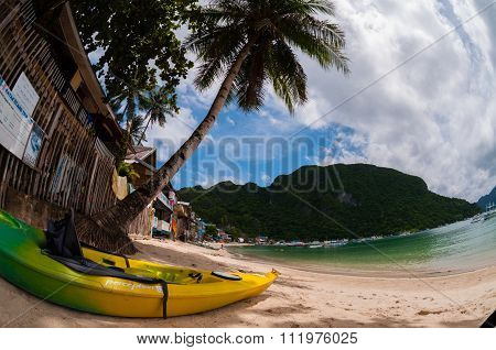 Yellow kayak laying on the sand beach with palm tree