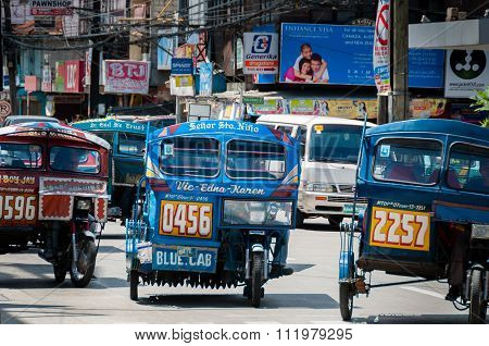 Blue Tricycles of Dumaguete driving on The Road