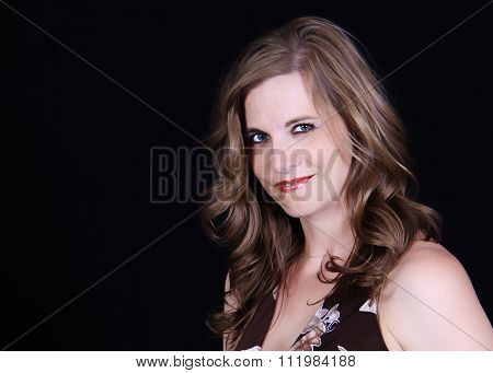Head and shoulder angled close up portrait of pretty blonde woman smirking at the camera on a black photographic background