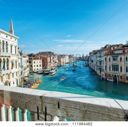 View of the Grand Canal, Venice, Italy looking over the stone balustrade of a balcony at the passing boat traffic and historic palaces below