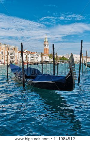 Covered gondola moored on the Grand Canal, Venice, Italy for traditional romantic tours of the canals of this ancient city and its lagoon