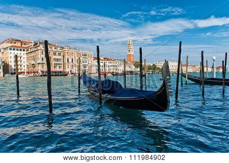 Gondola moored on the Grand Canal, Venice, Italy between traditional wooden mooring posts with a view looking across the canal towards the Campanile, sunny blue sky day