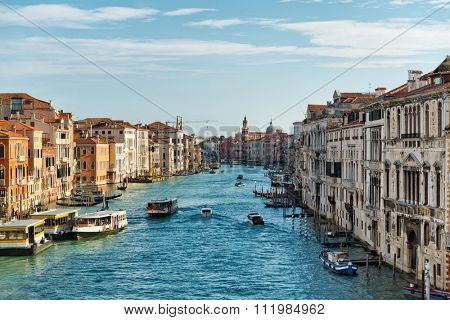 Grand Canal view, Venice, Italy looking down the length of the canal with vaporetti water buses , moored gondolas and private boats plying the water between historical architecture