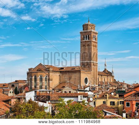 Scenic rooftop view of the Basilica dei Frari towering above the rooftops of Venice, Italy against a sunny blue sky