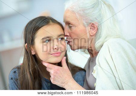 Little girl and grandma whispering secrets