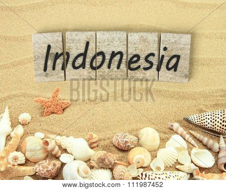 Indonesia on wooden board pieces with sea shells and sand
