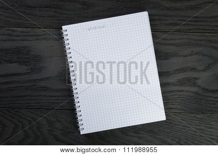 blank notepad with wishlist on gray wood table