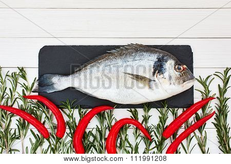 Fresh Dorado Fish On Cutting Board With Rosemary And Chilly Pepper On White Wooden Table. Top View,