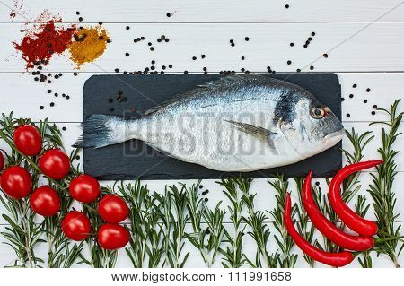 Fresh Dorado Fish On Slate Cutting Board With Rosemary, Cherry Tomatoes, Chilly Pepper. Top View