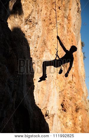 Silhouette Of Rock Climber Hanging On Belay Rope Againstthe Mountains
