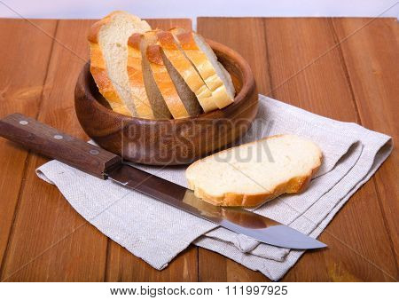 The Cut Bread In A Wooden Bowl Near A Big Knife On A Wooden Table