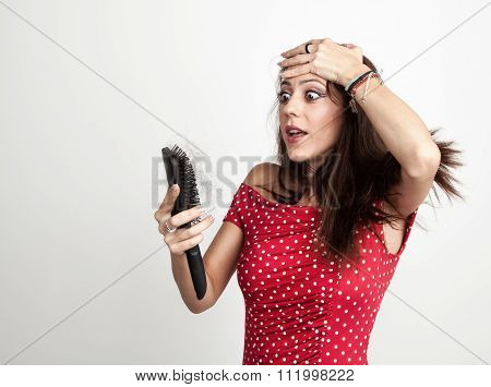 Astonished young woman holding brush