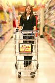 foto of grocery store  - a woman pushing a basket while shopping in the grocery store - JPG