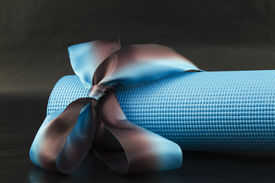 image of yoga mat  - Blue yoga with a blue and brown ribbon on a black background is a sharing of yoga - JPG
