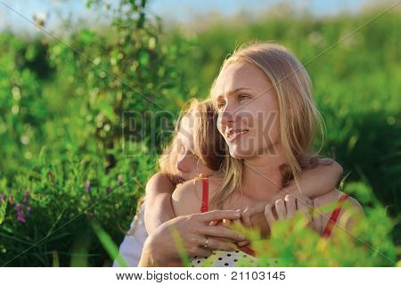 Beautiful Mother And Daughter Sitting On Green Lush Grass Meadow