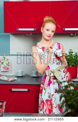 Chica rubia con taza de café en el interior de la cocina