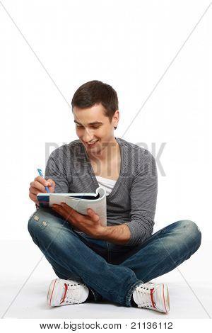 Un retrato de la longitud completa de un chico joven guapo universitario sentados en el suelo y estudiar, aislado o