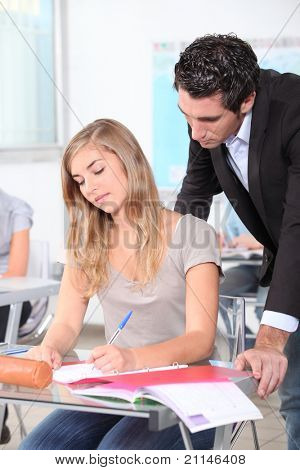 Teacher helping female student